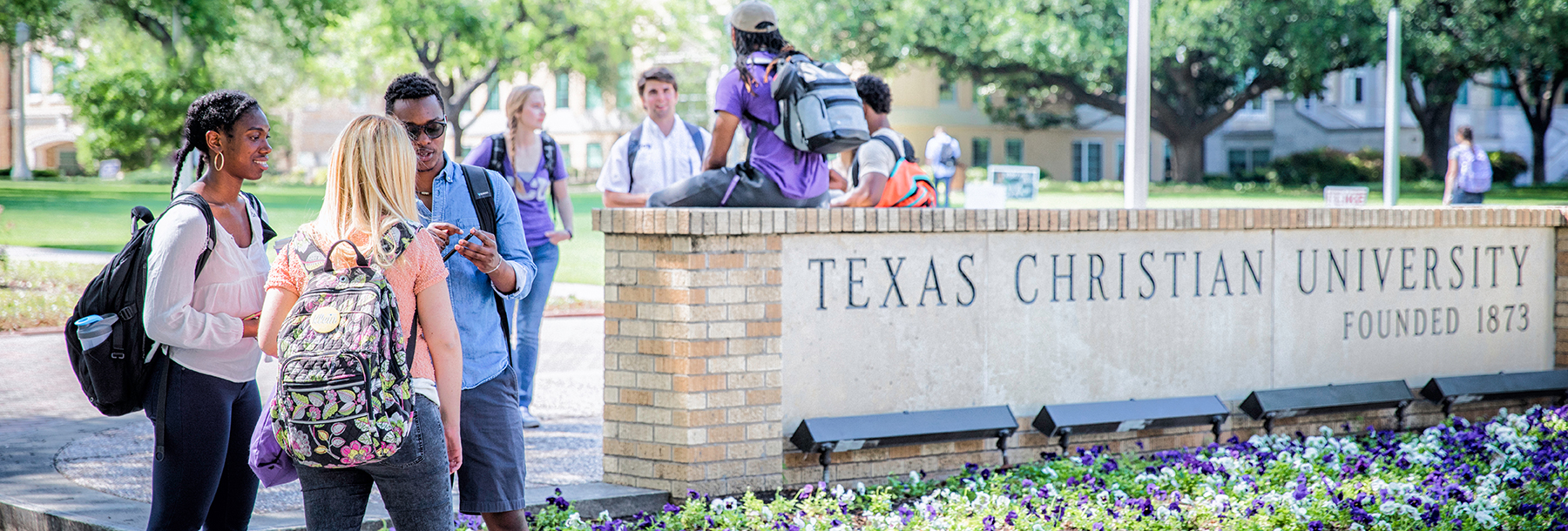 Section Image: diverse students at the TCU sign