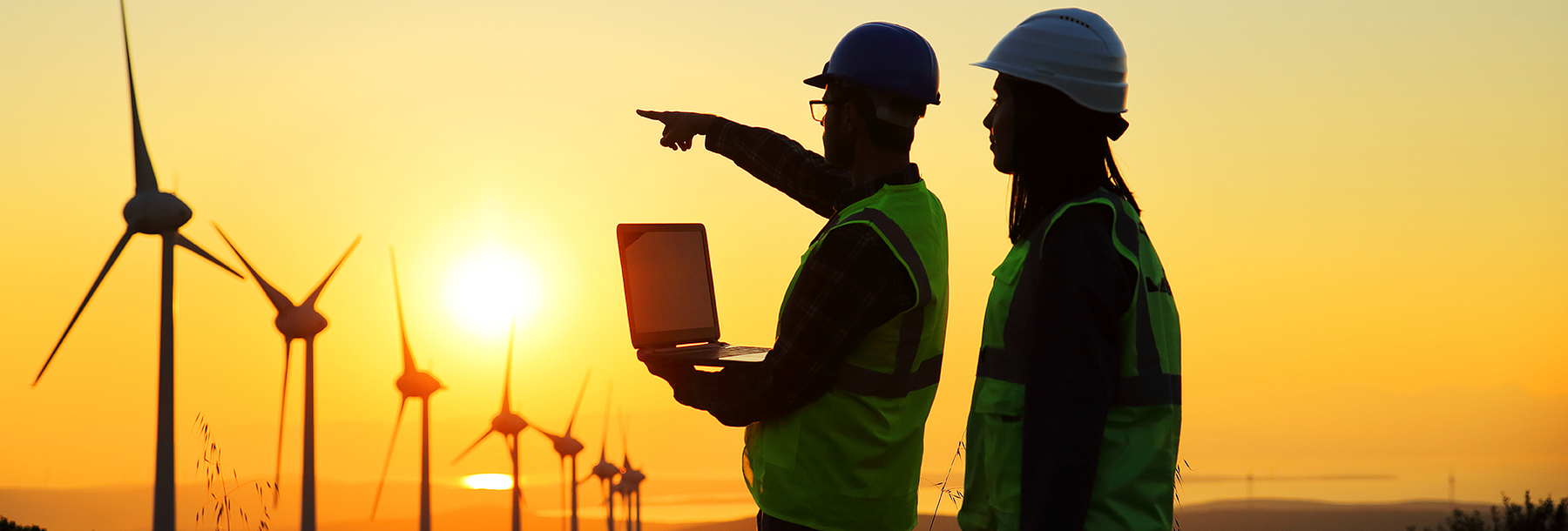 Section Image: Men with laptop observing windmills at sunset